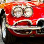 closeup of headlights of classic red car